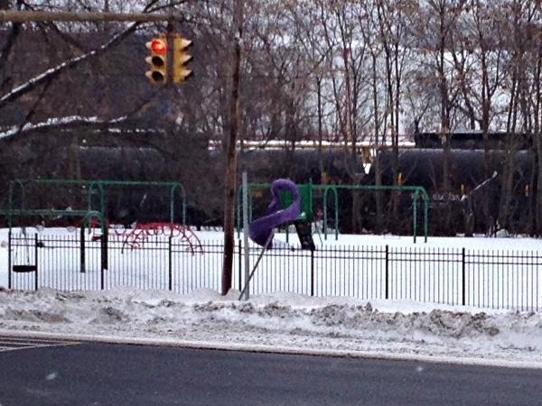 black oil tanker train behind playground