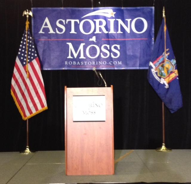 Stage with empty podium, American flag and New York State flag and banner for Astorino and Moss