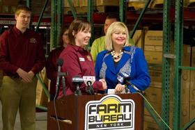 Sharon Smith, Executive Director of the Food Bank Association of New York State, accepts a donation from Nicole Rawleigh and the Young Farmers and Ranchers Committee.