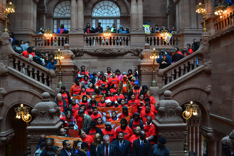 group of people in red t-shirts stand on staircase