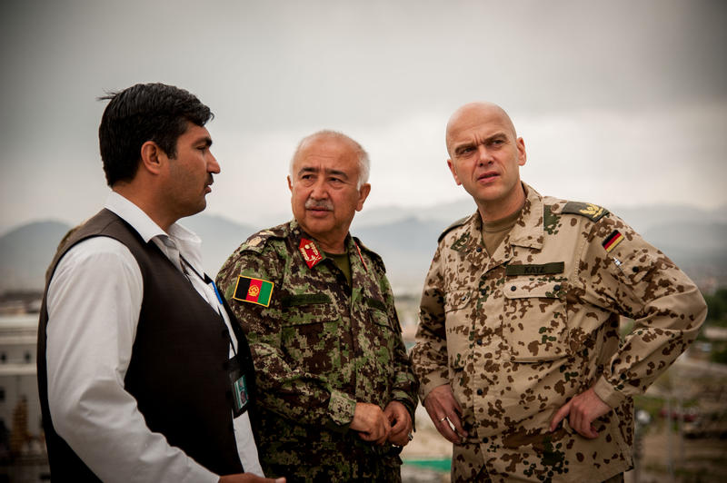 Aziz (left) working with Brigadier General Gunter Katz (right) and a commander from the Afghanistan National Defense University in Kabul, Afghanistan in 2013