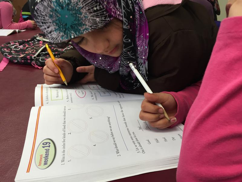 Aziz's daughter, Dewah (right), studies with a friend at the Islamic Center of Rochester