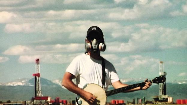 Image of a man wearing a gas mask playing a banjo