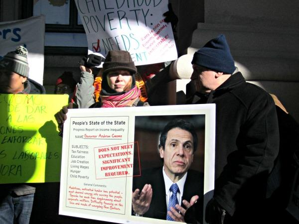 protesters bundled up outdoors with signs criticizing governor Andrew Cuomo