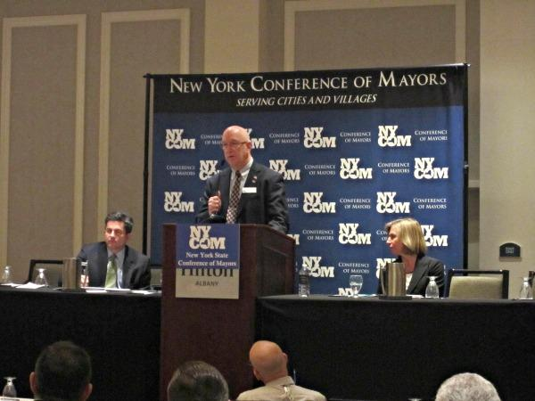 speaker standing at podium addressing the new york council of mayors