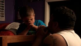 "TJ, one of the parents whose story is featured in ""American Winter,"" praying with his little boy"