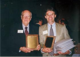 Jack Shelley (left) helps news reporter Rick Fredericksen with IPR awards won at the Iowa Broadcast News Association