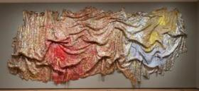 "A work by artist El Anatsui featured at the Des Moines Arts Center's exhibit, ""GRAVITY AND GRACE: Monumental Works by El Anatsui"""