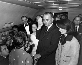 Judge Sarah T. Hughes administers the Presidential Oath of Office to Lyndon Baines Johnson aboard Air Force One, at Love Field, Dallas Texas. Mrs. Johnson, Mrs. Kennedy, Jack Valenti, Cong. Albert Thomas, Cong. Jack Brooks, Associate Press Secretary Malcolm Kilduff (holding microphone) and others witness