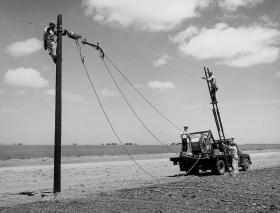 The Rural Electrification Administration erects power lines.