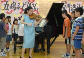 Midori Goto, born in Japan in 1971, one of the women who has reached the pinnacle of today's violin profession. (She also does serious educational outreach work, as in this picture.)