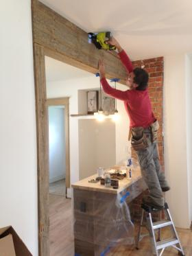 Siobhan Spain's brother installing reused barn wood in her kitchen.