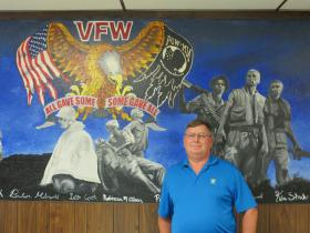 Retired Army Chief Warrant Officer Tim Mallot stands in front of a mural at the Tipton VFW Hall