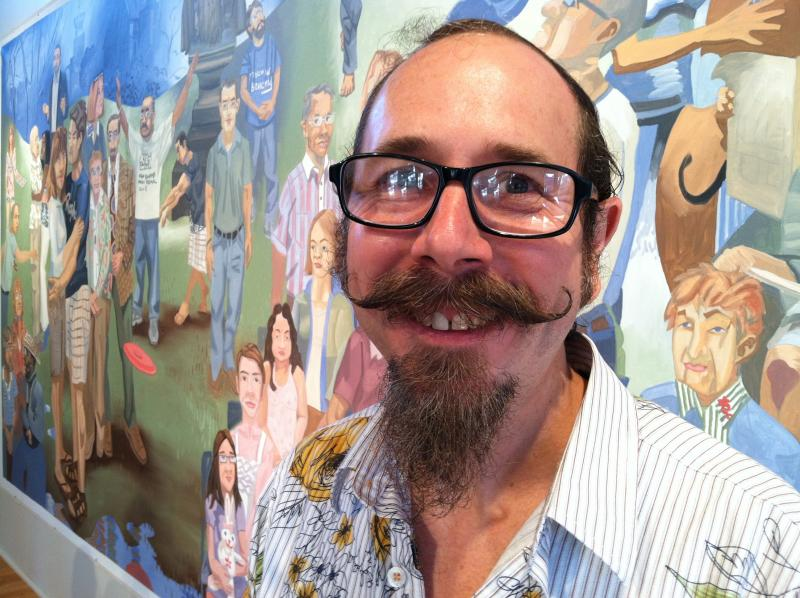 "Tom Torluemke and his mural ""You Know, We're all in this Together"" in a gallery at the CSPS in Cedar Rapids."