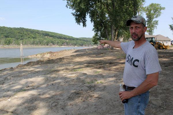 Bill Smith, president of the Missouri Valley Waterfowlers Association, stands along the Missouri River near a few homes built along the river. Smith is also a subcontractor and has worked on dozens of homes since last year's flood.