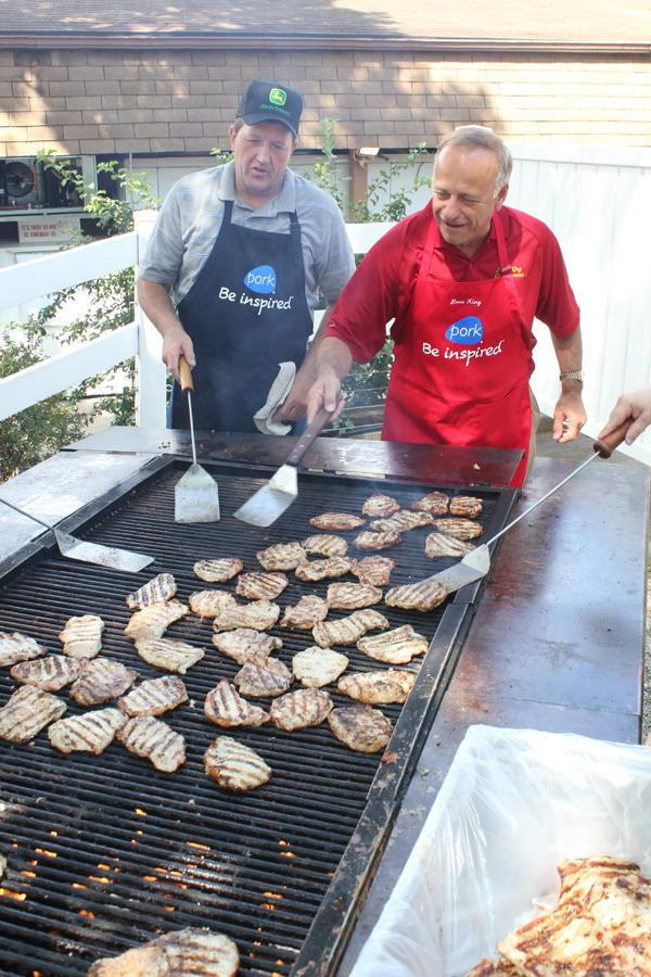 Republican Iowa Congressman Steve King (right) flips pork chops at the Iowa State Fair in Des Moines while Terry Aupperle of Wiota watches. Aupperle lives in Cass County, he can't vote for King anymore because of redistricting.