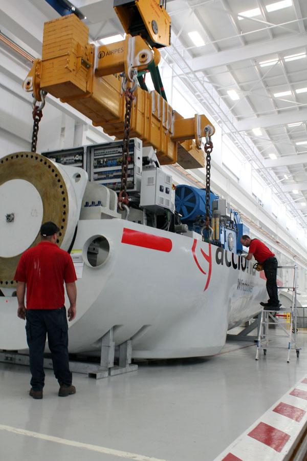 Workers at Acciona Wind Power in West Branch, Iowa assemble a casing around the nacelle of a wind turbine.