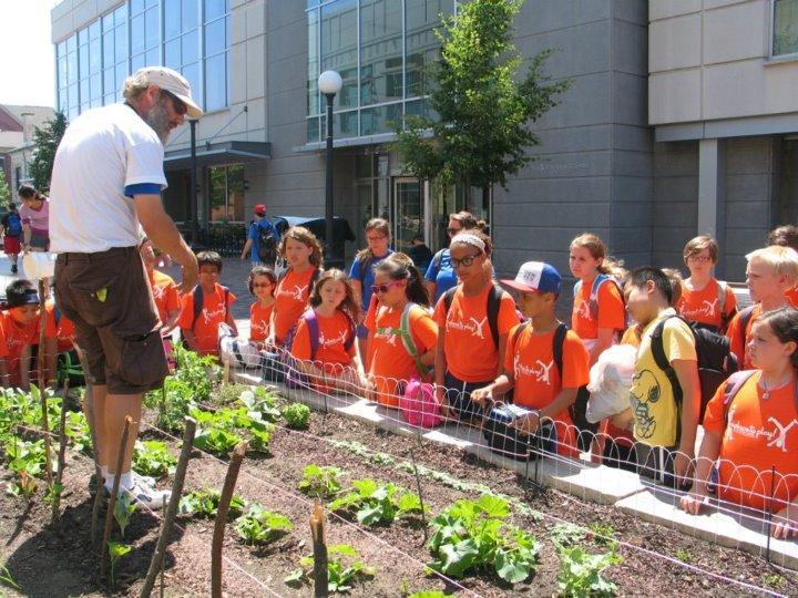 Scott Koepke during a gardening demonstration with children at the Iowa City Pedestrian Mall.