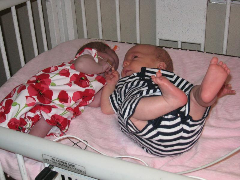 When put together in their crib, Aidan often moves over so he can touch his sister