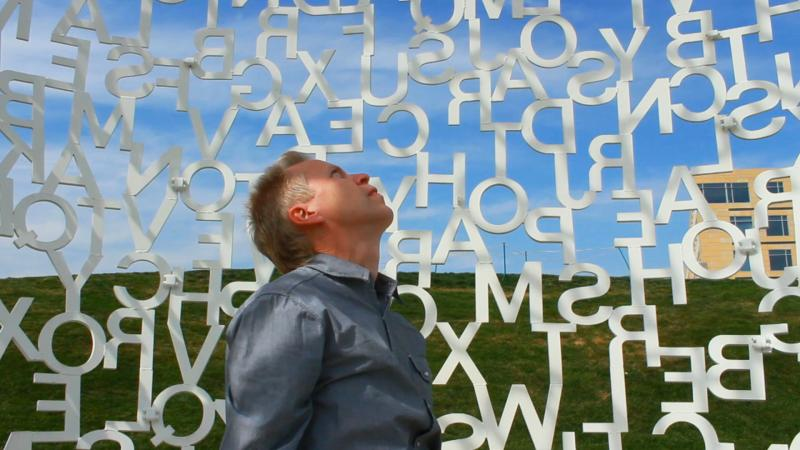 """""""Symphony In Sculpture"""" composer Steve  Heitzeg standing inside the sculpture """"Nomad"""" in the Pappajohn Sculpture Park."""