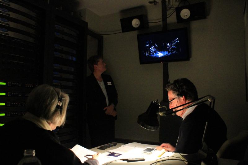Iowa Radio Reading Information Service (IRIS) volunteers Dorothy Hockenbery and Bobby Baily watch a closed circuit TV feed of Les Miserables with IRIS executive director Maryfrances Evans during an audio description backstage at the Civic Center.