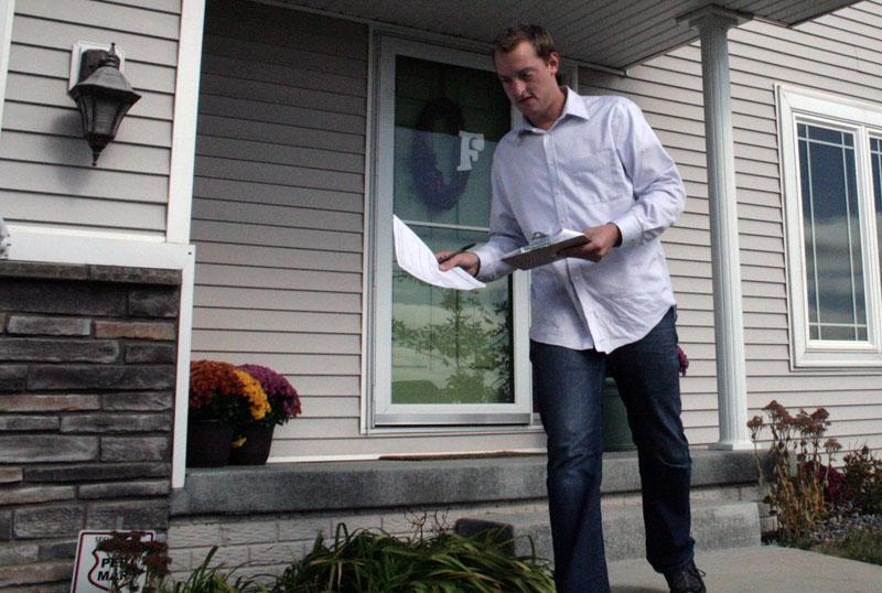 William Johnson knocks on doors in suburban Grimes in support of former Massachusetts Governor Mitt Romney.