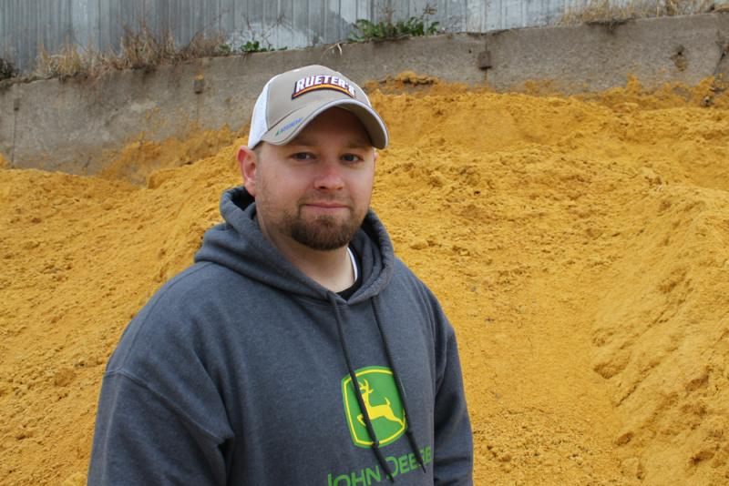 Josh Alexander stands next to a pile of distillers grain at his family's feedlot near Pilger, Neb.