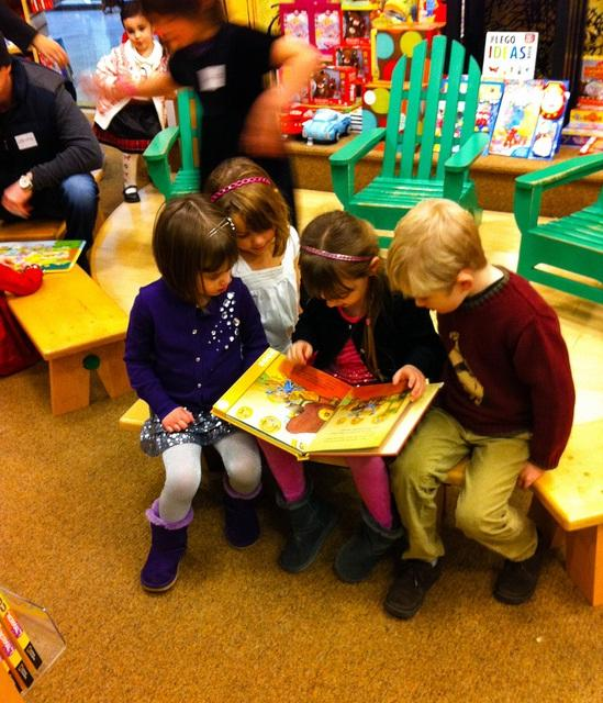 Group of children reading a book together.