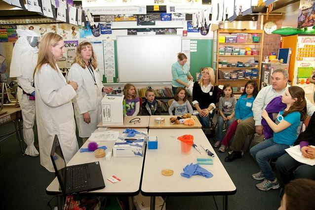 Employees of the U.S. Army Edgewood Chemical Biological Center and U.S. Army Research Laboratory discuss science experiments for children and parents at Youth's Benefit Elementary School