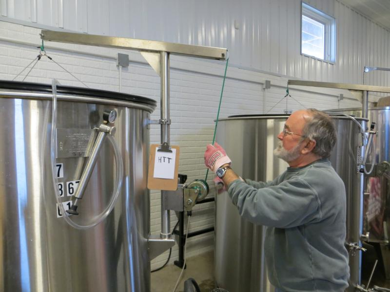 Winemaker John Larson mixes wine in a tank at his winery and vineyard in northern Iowa.
