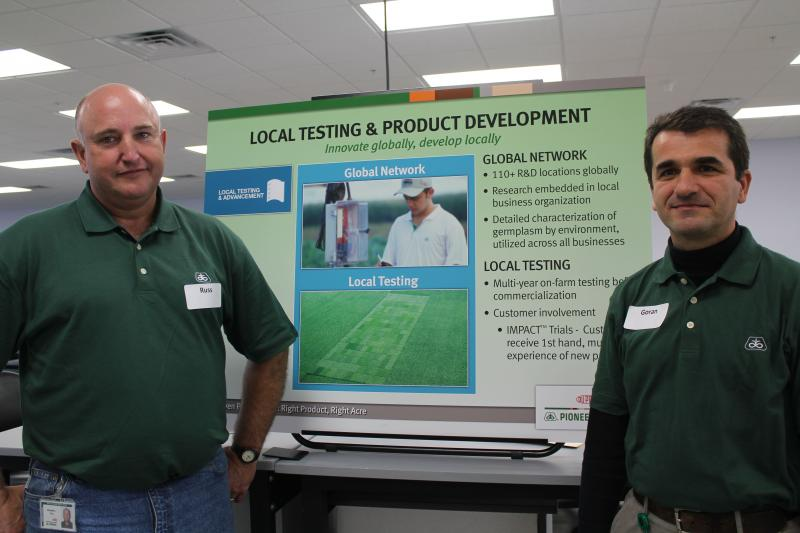 DuPont Pioneer research scientists Russ Fox (left) and Goran Srnic explain local seed testing to visitors at a company open house.