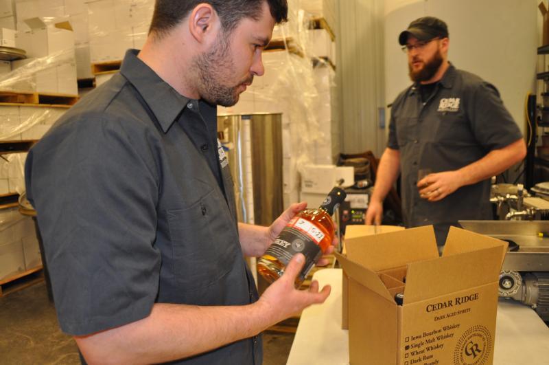 An employee labels a bottle of single-malt whiskey.