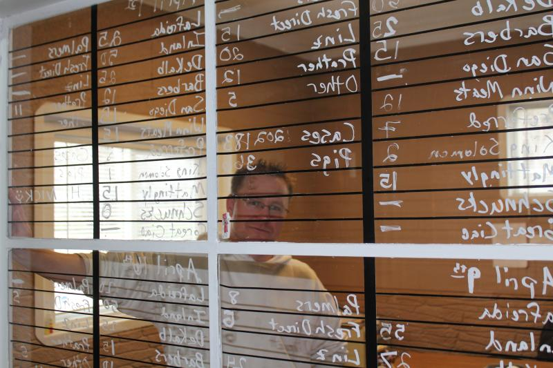 Nick Jones, general manager of Eden Farms in Des Moines, Iowa, keeps track of sales on a window in his office.