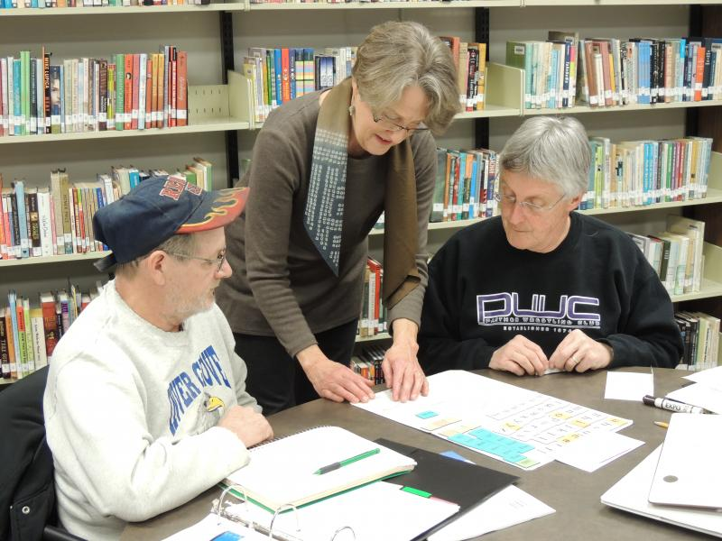 Coordinator of the Adult Literacy Center at Drake University Anne Murr, center, with Fred Dake, left, and volunteer tutor Jerry Walker, right.
