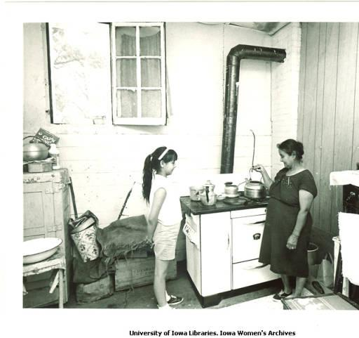 Migrant workers Virginia and Julia Guzman in kitchen, Cerro Gordo County, Iowa, 1960s.