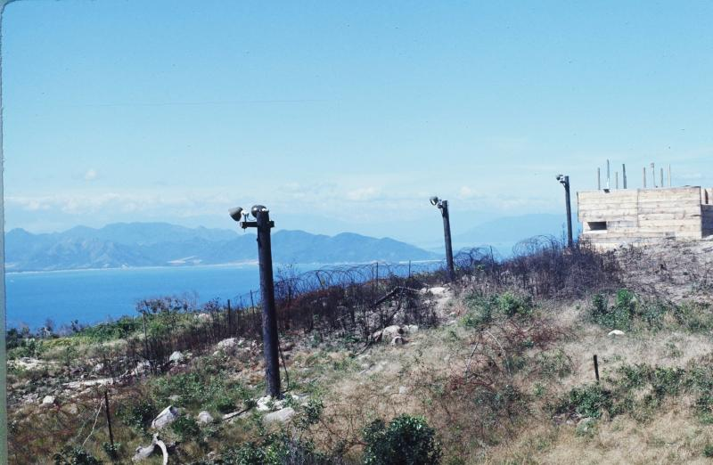A typical perimeter around a U.S. base, with barbed wire, flood lights and bunker. Hon Tre, 1970.