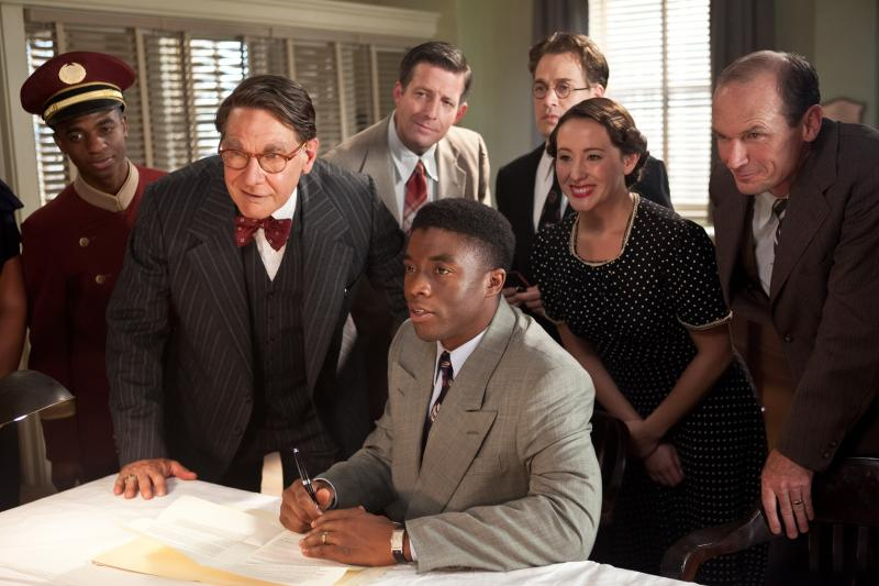 Branch Rickey (Harrison Ford), Jackie Robinson (Chadwick Boseman), Harold Parrott (TR Knight, standing), Miss Bishop (Rhoda Griffs) and Clyde Sukeforth (Toby Huss)