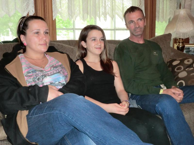12-year-old Dezirea Hughes sits with her family in a friend's living room.