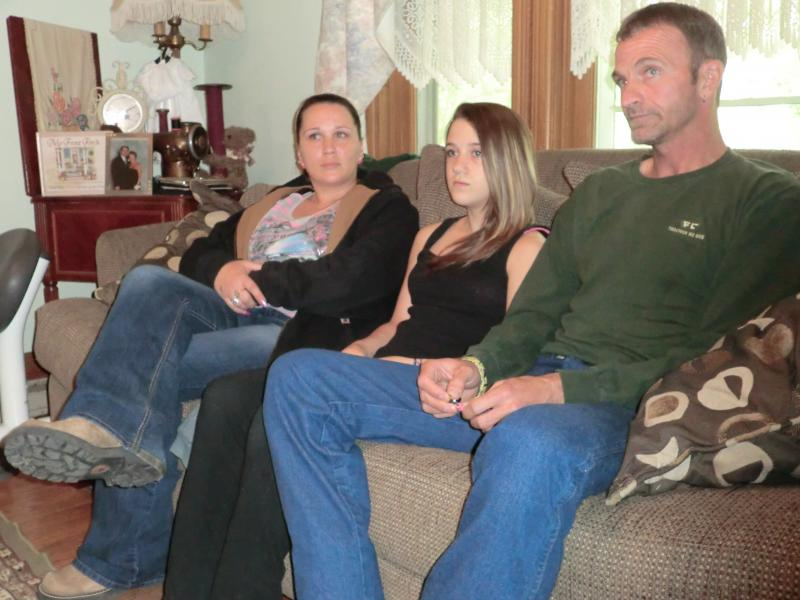 12-year-old Dezirea Hughes, who escaped the abduction and alerted authorities, sits with her family.