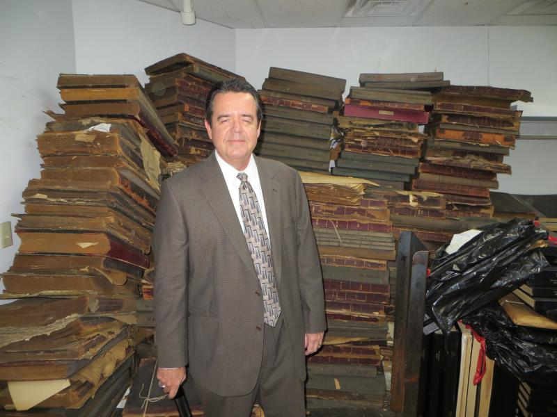 Kevin Johnson is surrounded by bound volumes of old newspapers, going back to the 1800s.