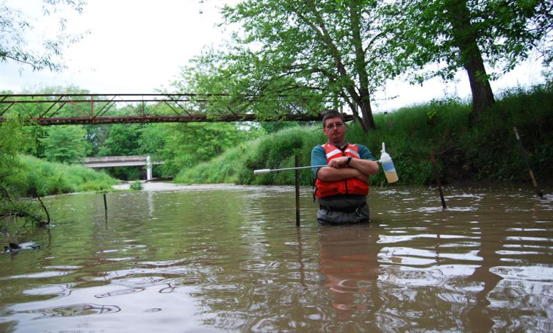 U.S. Geological Survey Chemist Dave Alvarez is in Goodwater Creek near Centralia, Mo., to collect some stream water.