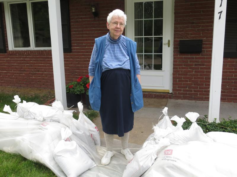 Donnarae MacCann stands by a wall of sandbags surrounding her home on Normandy Drive, in Iowa City.