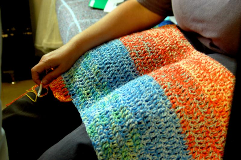 A prisoner knits an afghan to help pay for restitution to victims.