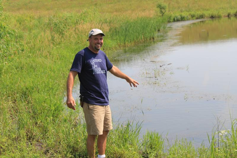Seth Watkins says this pond was cloudy from sediment runoff until he cleared cedar trees and scrub brush from an adjacent patch of prairie. With the long roots of the grasses holding soil and trapping nutrients, the pond cleared up.