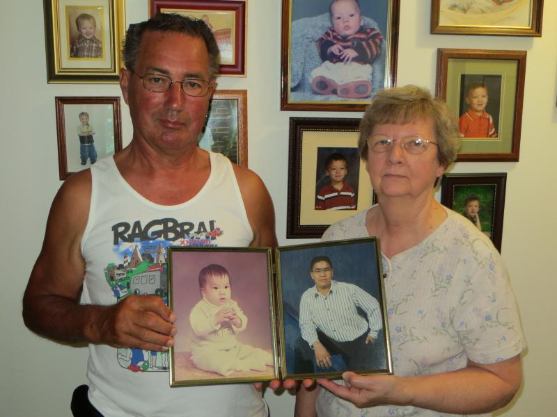 Alan and Lorena Van Der Kamp hold pictures of son Mark. Photos on the wall are grandson Blake.