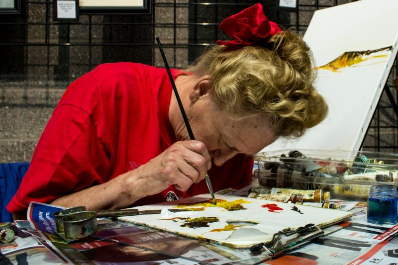 Because Elsie Monthei is legally blind, she gets as close as possible to her color palette while mixing oil paints at the Iowa State Fair. She is part of Very Special Arts (VSA).