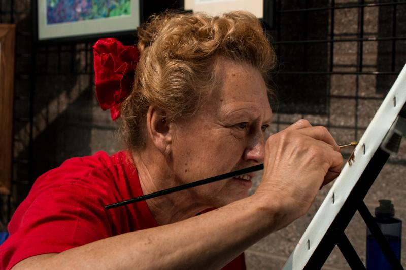 Elsie Monthei is a legally blind painter demonstrating for Very Special Arts (VSA), group highlighting artists with disabilities. Monthei is creating an oil painting of a Texas landscape from a photograph.