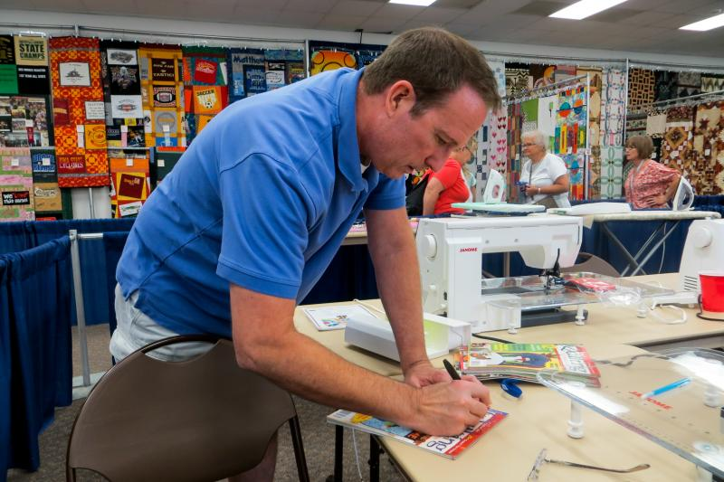 Quilter Patrick Lose signs an autograph during the 2013 Iowa State Fair. He returned to his home from Phoenix to give quilting classes at the fair for one week.
