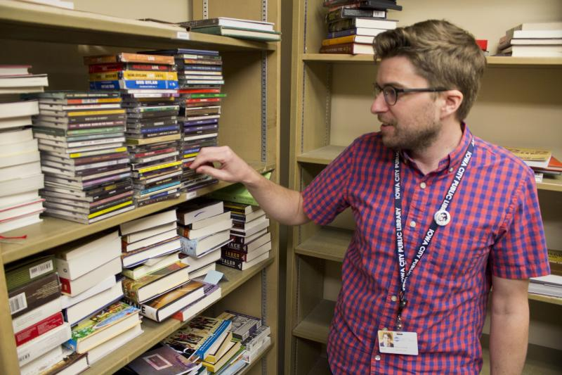 Iowa City Librarian Jason Paulios looks at recently organized CDs that were donated to the library. Paulios says he gets a lot of donations when school at the University of Iowa starts and ends as students come and go on campus.