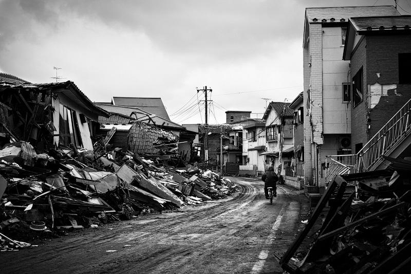 A man biking through the rubble three months after the 2011 Japanese tsunami and earthquake that killed almost 16,000 people.